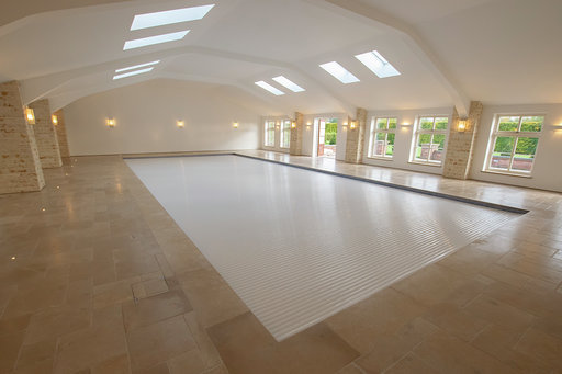 Indoor pool with white slatted cover on